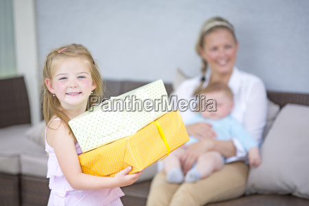 girl holding gifts with baby boy