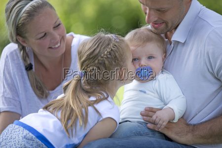 young girl kissing baby brother on
