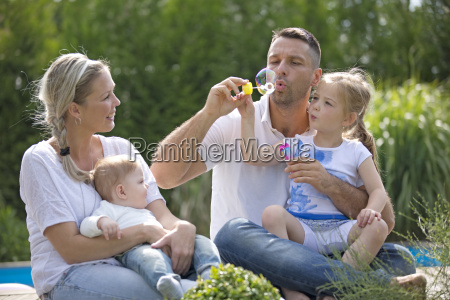 father blowing bubbles with daughter and