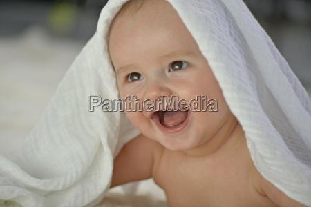 baby boy under white towel smiling