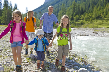 family hiking next to stream portrait