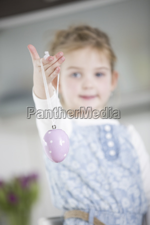 young girl holding easter egg ornament