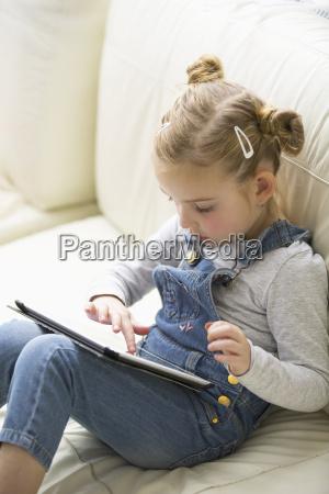 young girl sitting on sofa and