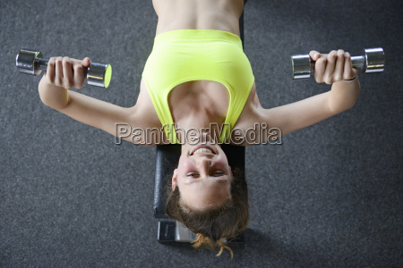 teenage girl bench pressing with dumb