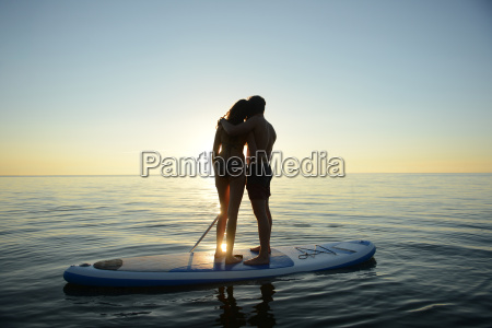 teenage couple watching sunset from paddleboard