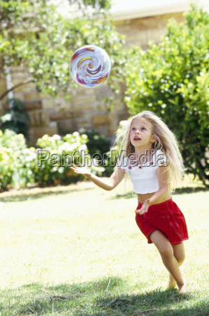 young girl chasing ball outdoors