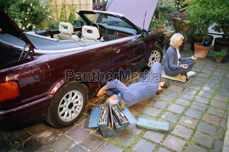 mature man fixing car woman doing