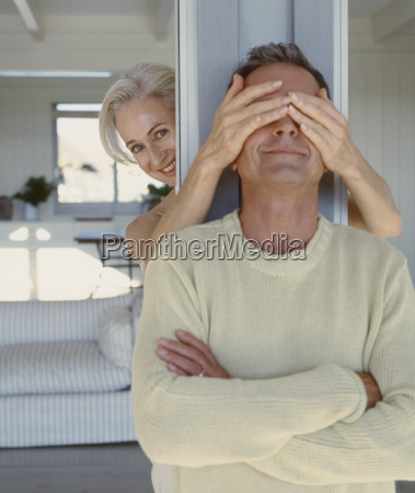 mature woman covering her husbands eyes