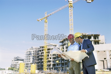 construction worker and businessman looking at