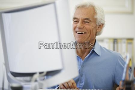 man smiling while looking at computer