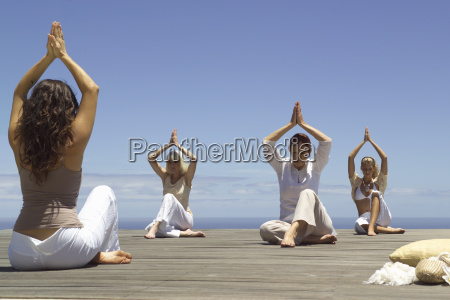 group of women practicing yoga on