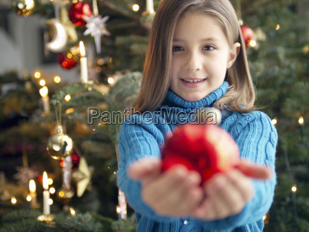 girl holding christmas ornament in outstretched