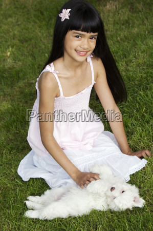 young girl with puppy in grass