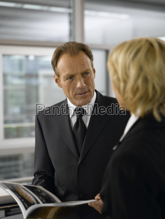 businessman and businesswoman talking in office