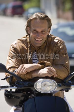 man sitting on motor scooter smiling