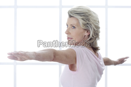 senior woman with arms outstretched indoors