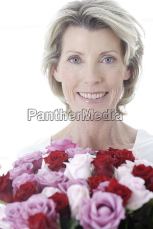 senior woman smiling and holding bouquet