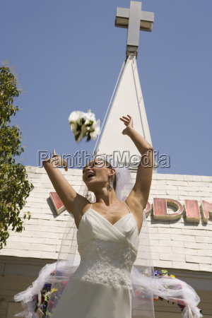 bride throwing bouquet in front of