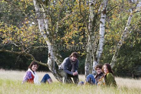friends sitting next to tree