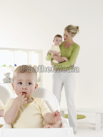 baby in highchair with mother and