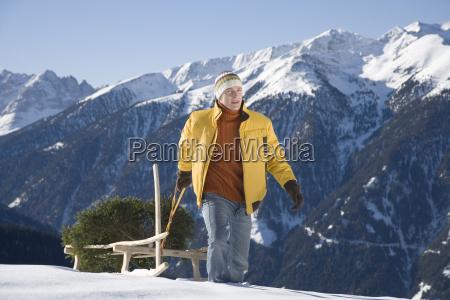 man pulling pine tree on sled