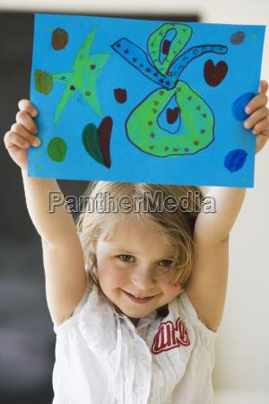 preschool girl holding up artwork