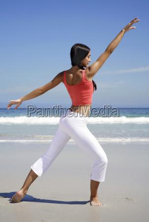 woman practicing yoga at beach