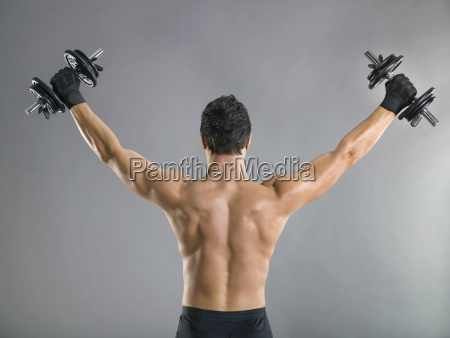 rear view of man lifting weights