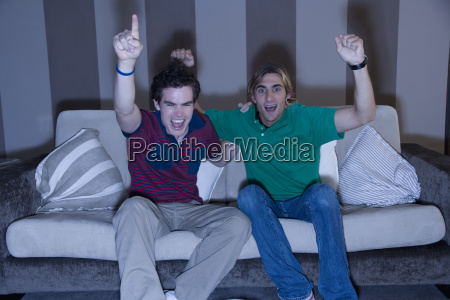 two young men cheering on sofa