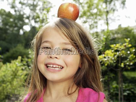 young girl balancing apple on head