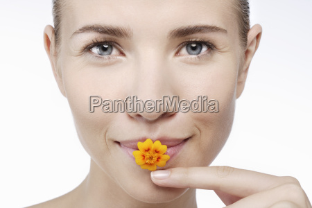 young woman with flower in mouth