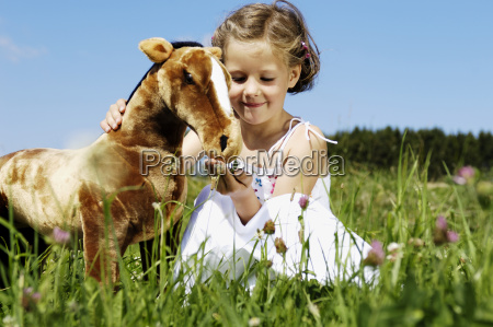 young girl feeding stuffed animal horse