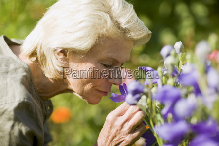 senior woman smelling flowers