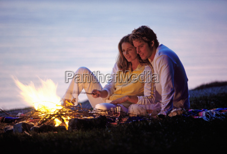man and woman sitting beside campfire