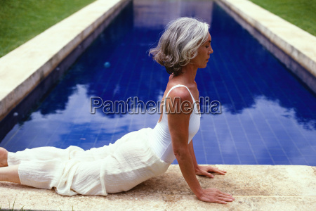 middle aged woman stretching by pool