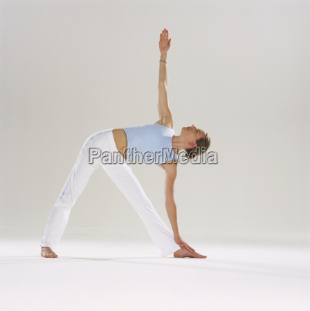 woman doing yoga leaning over and