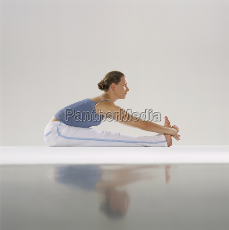 woman stretching in yoga pose touching