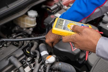 mechaniker pruefen batterie mit multimeter