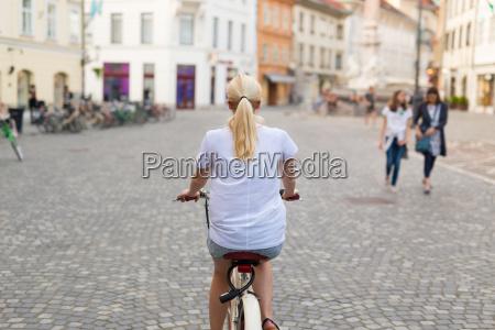 beautiful blond caucasian woman riding bike