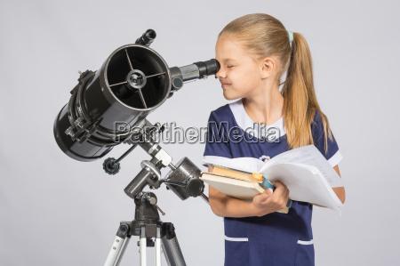 school girl looking through a telescope