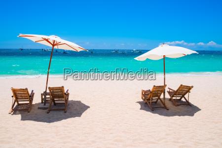 weisser sandstrand mit sonnenschirmen und stuehlen