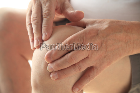 senior has hands on his aching
