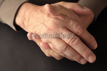 older man holding his numb hand