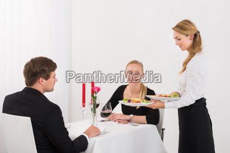 waitress serving food to couple