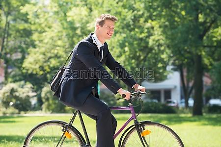 geschaeftsmann reitfahrrad im park
