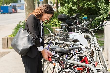 junge geschaeftsfrau sperren ihr fahrrad
