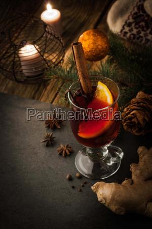 gluehwein mit gewuerzen und weihnachtsdekoration vertikal