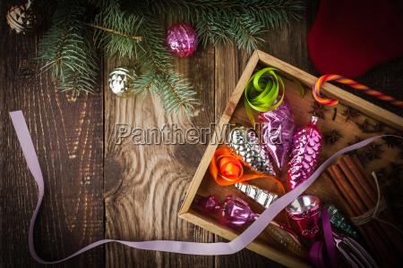 holzkiste mit weihnachtsbaumdekoration und gewuerzen horizontal