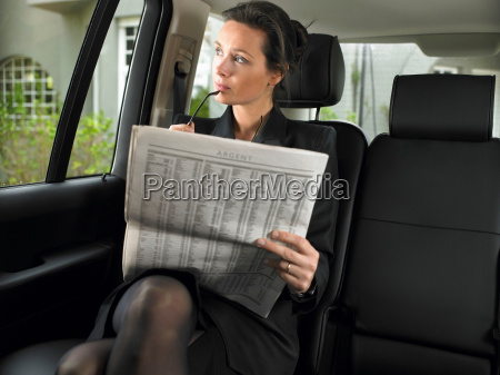 woman in car reading newspaper