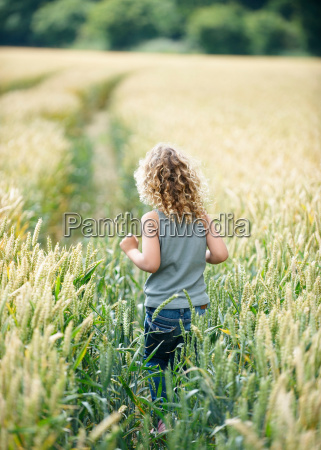 young girl walking path in cornfield